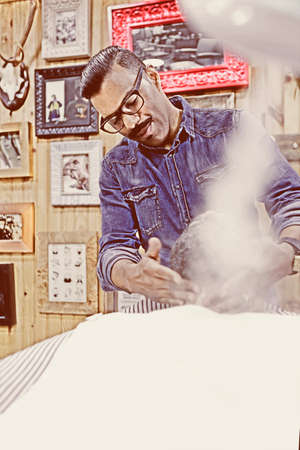 steam machine: barber is steaming with a steam machine to a beard of a customer on a beard shaving session in a barber shop - focus on the left eye
