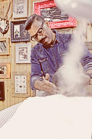 MAQUINA DE VAPOR: barbero es al vapor con una m�quina de vapor para una barba de un cliente en una sesi�n de afeitar la barba en una peluquer�a - se centran en el ojo izquierdo Foto de archivo