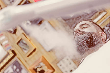 MAQUINA DE VAPOR: Frente a un cliente se cuece al vapor con una m�quina de vapor en una sesi�n de afeitar la barba en una peluquer�a - se centran en el ojo