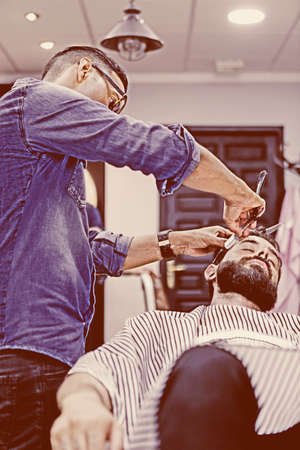 barber chair: hairstylist on a beard shaving session and a customer on a barber chair on the barber shop - focus on the barber face Stock Photo