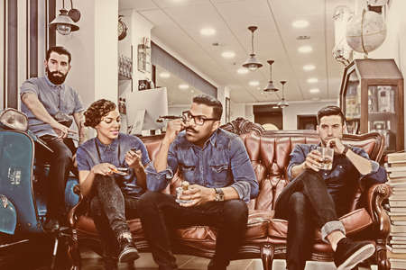 barbershop: portrait of a hairstylist with his staff sitting on a couch on their break time at his barber shop - focus on the barber face Stock Photo