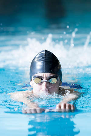 swim cap: young male swimmer swimming with a swim board doing leg exercises in an indoor swimming pool - focus on the face