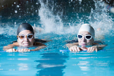 couple of female swimmers swimming with a swim board doing leg exercises in an indoor swimming pool - focus on the right woman face Banque d'images