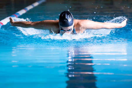 female swimmer is swimming butterfly stroke in an indoor swimming pool - focus on the head