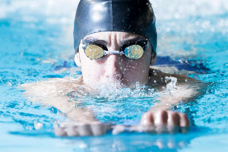 closeup of a male swimmer swimming with a swim board doing leg exercises in an indoor swimming pool - focus on the face Stock Photo