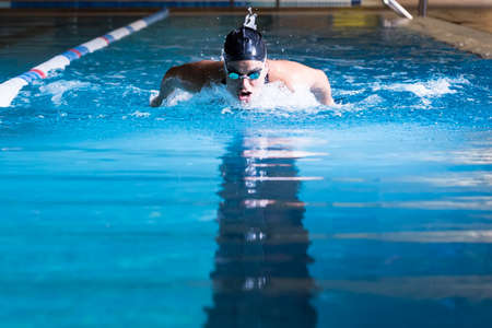 female swimmer is taking breath while is swimming butterfly stroke in an indoor swimming pool - focus on the head Standard-Bild