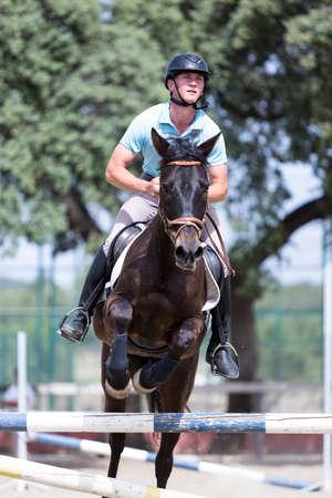 junge männliche Reiter wird an der Kuhstall mit einem braunen Pferd - Fokus auf das Gesicht Standard-Bild