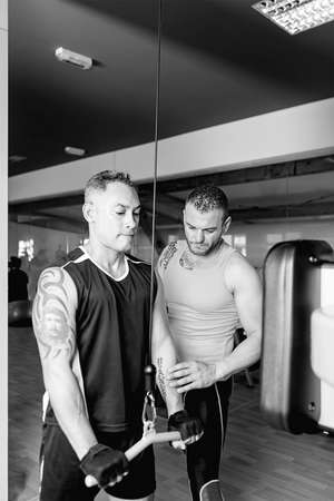 tricep: personal trainer helping young man making pulley pushdown standing - tricep exercise - finish exercise - focus on the trainer face