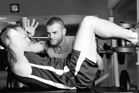 personal trainer helping young man making abdominal exercise on a bench - at the gym - focus on the trainer right eye