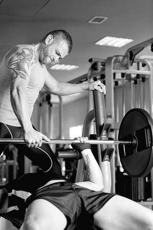 personal trainer: personal trainer helping young man making barbell press bench - chest exercise - at the gym - finish exercise - focus on the trainer face