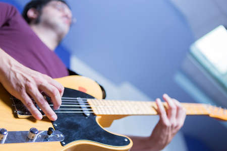a rehearsal: view from below of a musician playing an electric guitar in a rehearsal session at the recording studio - focus on the right middle finger