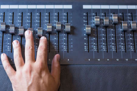 sound studio: detail of the hand of a sound professional adjusting a sound mixing desk at the recording studio - focus on the middle finger