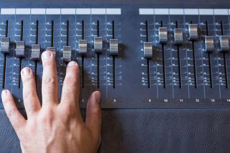 estudio de grabacion: detalle de la mano de un profesional de ajustar un sonido mesa de mezclas en el estudio de grabación de sonido - centrarse en el dedo medio