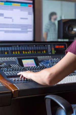 estudio de grabacion: mano de un ingeniero de sonido ajustando una mezcla de sonido escritorio mientras un cantante está ensayando en el estudio de grabación - se centran en la mano