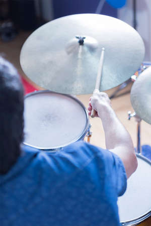 subjective: subjective view of a drummer playing drums in a recording studio - focus on the drumstick Stock Photo