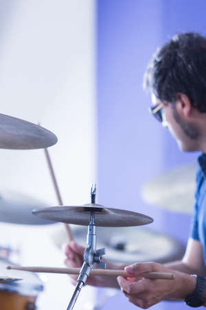 cymbal: closeup of a cymbal with an unfocused drummer playing the drums on background in a recording studio - focus on the cymbal Stock Photo