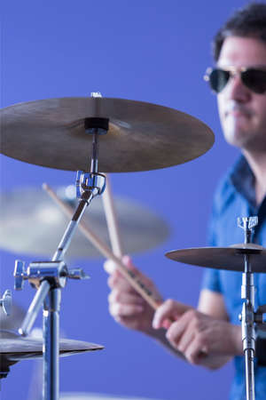 cymbal: closeup of a cymbal with an unfocused drummer playing the drums and holding the drumsticks on background in a recording studio - focus on the cymbal