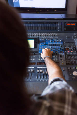 subjective: subjective view of a hand of a sound professional adjusting a sound mixing console at the recording studio - focus on the hand