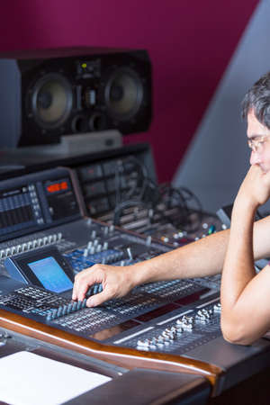audio mixer: concentrated sound professional adjusting a sound mixing desk at the recording studio - focus on the right hand