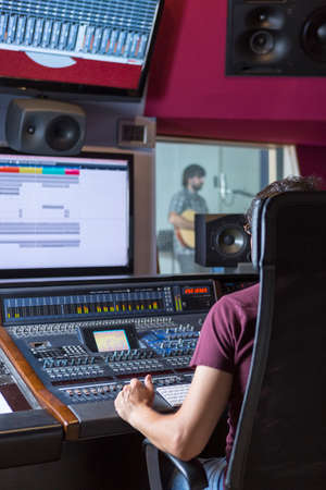 production engineer: sound professional working on the recording studio with a sound music console and a singer rehearsing at the rehearsal room - focus on the hand
