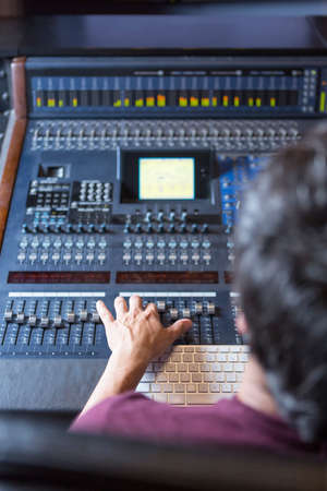 subjective: subjective view of a hand of a sound professional adjusting a sound mixing desk at the recording studio - focus on the hand