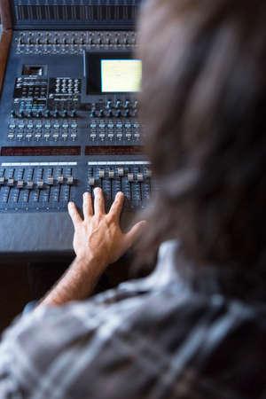 ミキシング デスク中指に焦点を当てる - レコーディング スタジオで音を調整するサウンド エンジニアの手の主観ビュー
