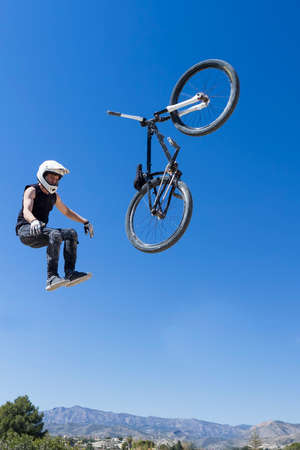 bmx bike: young BMX cyclist falling down from air with his BMX bike on a BMX session in the mountain - focus on the left arm Stock Photo