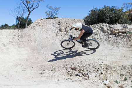 trail bike: young man BMX biker riding with his bike on a BMX circuit in the mountain - focus on the back