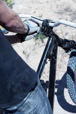 bmx bike: back view of the hands of a BMX cyclist adjusting the handlebar of the BMX bike - focus on the middle of the handlebar