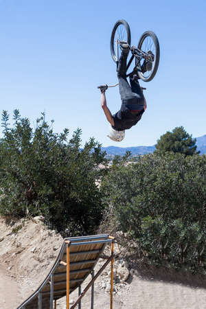 bmx bike: BMX biker performs high-flying BMX stunt with a BMX bike on a BMX session in the mountain - focus on the right leg