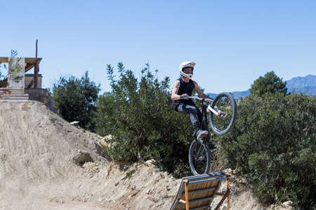 bmx bike: young man jumping with BMX bike using a ramp on a BMX session in the mountain - focus on the body