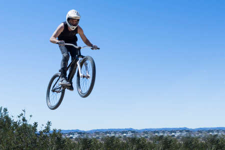 bmx bike: young man jumping with BMX bike on a BMX session in the mountain - focus on the body
