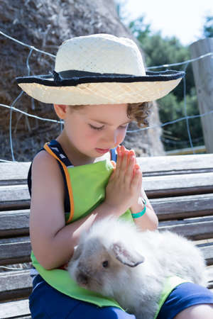 detail of a young boy farmer caressing a rabbit sitting on a bench at the farm - focus on the left eye Banco de Imagens
