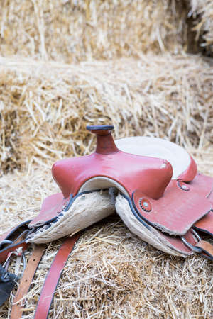 horse saddle: horse saddle on a hay bale useful as a horseriding background - focus on the horn