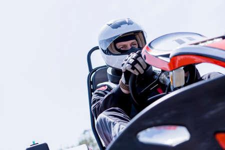 van onderen bekijken van een geconcentreerde gokart piloot op de startlijn voor het starten van een race in een openlucht karting circuit - focus op het rechteroog