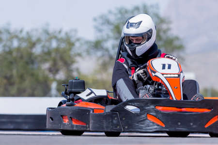 go to: young man go-kart pilot is racing a race in an outdoor go karting circuit - focus on the helmet