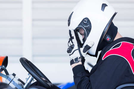 carting: profile view of a concentrated karting pilot sitting on his go-kart before starting a race in an outdoor go karting circuit - focus on the eye