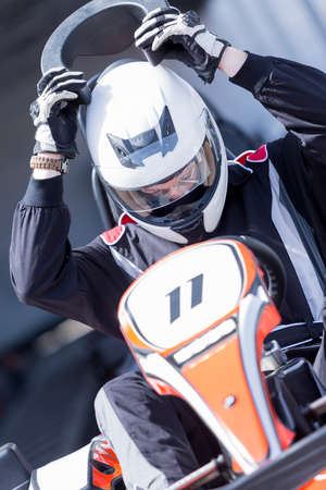 carting: closeup of a karting driver putting on the neck brace before starting a race in an outdoor go karting circuit - focus on the face