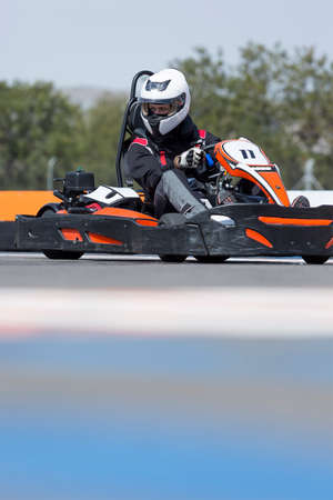 carting: young man go-kart driver is racing a race in an outdoor go karting circuit - focus on the helmet