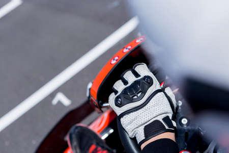 subjectieve kijk van de hand van een go-kart piloot met het handwiel op de startlijn voor het starten van een race in een openlucht karting circuit - focus op de handschoen Stockfoto