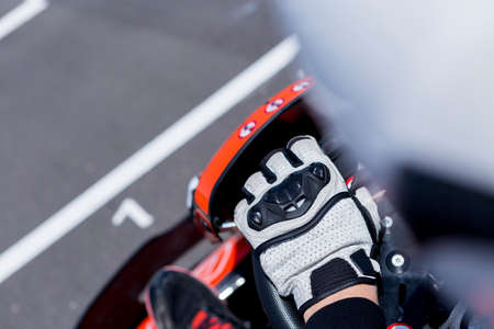 subjective view of the hand of a go-kart pilot holding the handwheel on the starting line before starting a race in an outdoor go karting circuit - focus on the glove Stock Photo