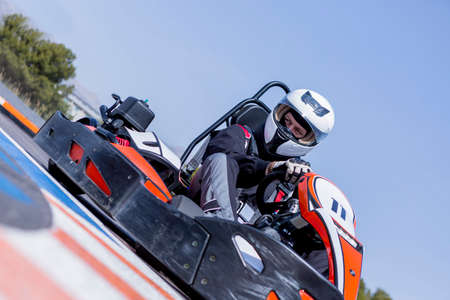 carting: young man go-kart racer is racing a race in an outdoor go karting circuit - focus on the left eye Stock Photo
