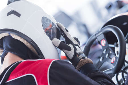 back view of a concentrated karting pilot sitting on his go-kart before starting a race in an outdoor go karting circuit - focus on the thumb