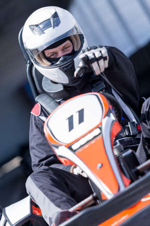 closeup of a karting driver pointing with the finger on a challenging sign before starting a race in an outdoor go karting circuit - focus on the face Stock Photo