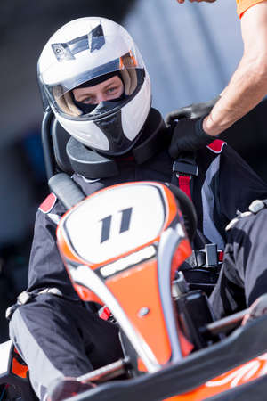 safety harness: engineer is fasten the safety harness of a gokart pilot before starting a race in an outdoor go karting circuit - focus on the face Stock Photo