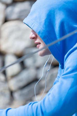 running nose: portrait of a young male runner profile is resting listening music after a running session outdoor - focus on the nose Stock Photo