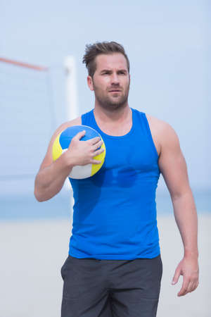 Volley: portrait of a young man is holding a volley ball on a volley sand court at the beach - focus on the eyes