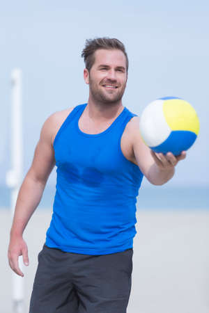 beach volley: smiling young man is offering the ball during a beach volley match on a sand court at the beach - focus on the eyes Stock Photo
