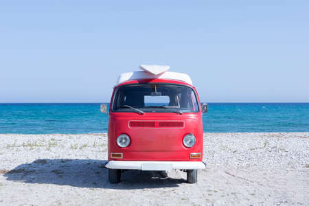 front view of a red and white classic van with a surfboard on the top on the beach - useful as a surf background