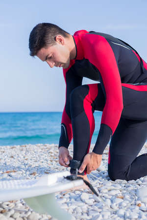 neoprene: young man with a wetsuit is adjusting the leash of a surf board to the ankle on a surf session on the beach - focus on the left hand